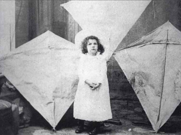 William Eddy's daughter Margaret poses with her father's kites in 1895. Photo by William Eddy, via WikiCommons.