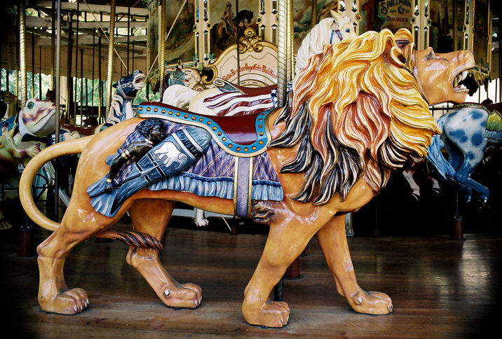 This outside-row Herschell-Spillman lion, at the 1914 carousel at Golden Gate Park in San Francisco, has a caricature of an African warrior hanging out on its saddle blanket. (© Aaron Shepard, via carousels.org)