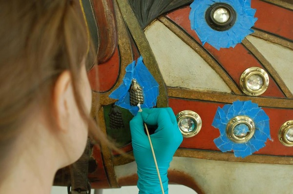 A conservation intern at the Shelburne Museum removes linseed oil from a 1906 Dentzel carousel horse. (Via the Shelburne Museum's Dentzel Carousel Facebook page)