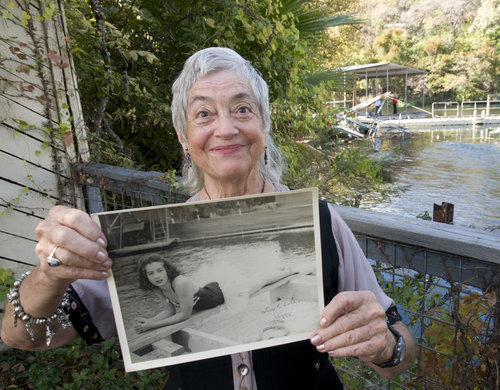 Peggy Sparks holds a photo of herself taken when she worked at Aquarena. Image by Andy Sharp for the American Statesman..