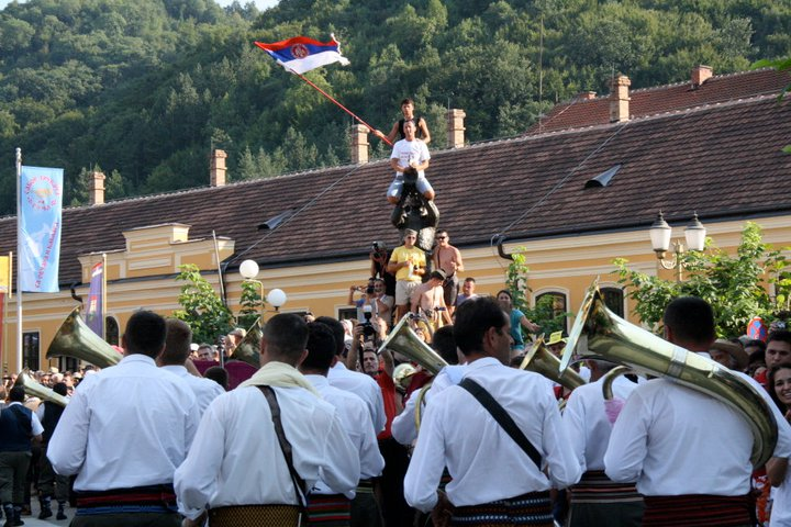 "Demiran Ćerimović Orchestra approaches a flag-waver on a statue. The Guča Trumpet Festival is a big source of national pride, hence its not uncommon to see attendees waving the Serbian flag. (Still from ""Brasslands"" courtesy of the Meerkat Media Collective)"