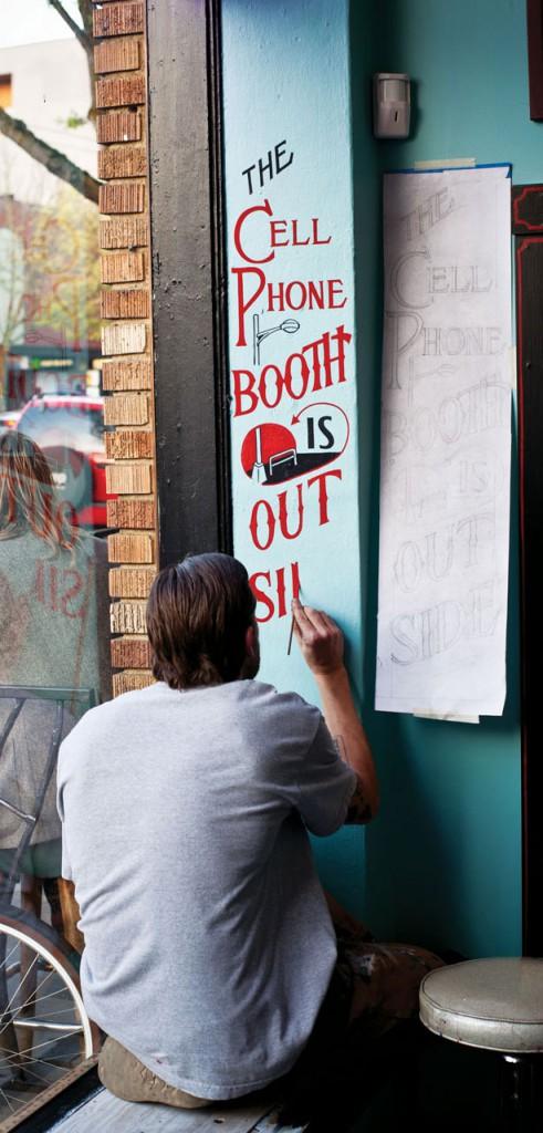 Sean Barton paints a tongue-in-cheek sign in Seattle, Washington. Courtesy Princeton Architectural Press.