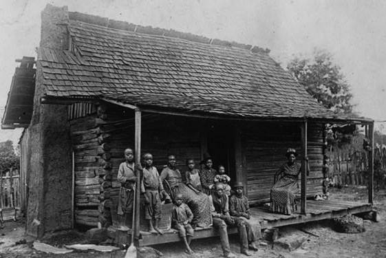 A family of sharecroppers outside their cabin near Eufala, Alabama. (Via Library of Congress)