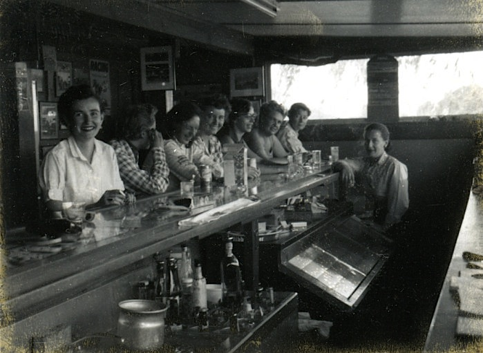 Above: Women crowd the bar at the Pyramid Lake Guest Ranch north of Reno. Top: A postcard from the 1940s depicts the practice of tossing one's wedding ring into the Truckee River from the Virginia Street Bridge after being granted a divorce. Both photos courtesy Special Collections, University of Nevada-Reno Library.