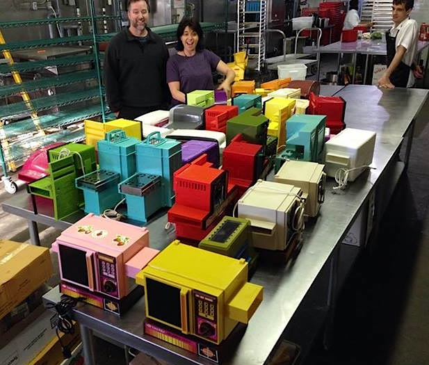 """Above: Todd Coopee (left) and Donna Henhoeffer, events manager of the Art Is In Bakery in Ottawa, with his collection of Easy-Bake Ovens, just before the book-launch party for """"Light Bulb Baking."""" Top: A 1981 Easy-Bake Mini-Wave Oven, just like the the one my brother and I destroyed. (Photos courtesy of Coopee)"""