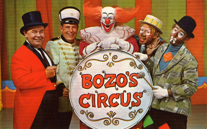 "Postcard photo of the main cast of Chicago's ""Bozo's Circus"" in 1968. From left: Ringmaster Ned (Ned Locke), Mr. Bob (bandleader Bob Trendler), Bozo (Bob Bell), Oliver O. Oliver (Ray Rayner), and Sandy (Don Sandburg)."
