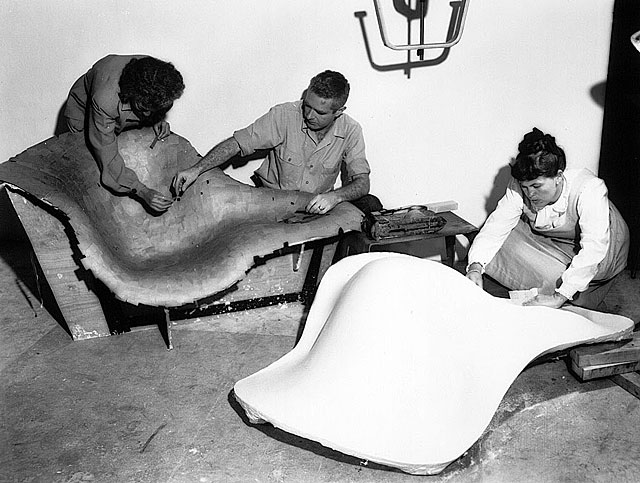 Powerhouse Mid-Century Modern furniture designer couple Charles and Ray Eames work on some of their famous chairs. (Via Teakhound)