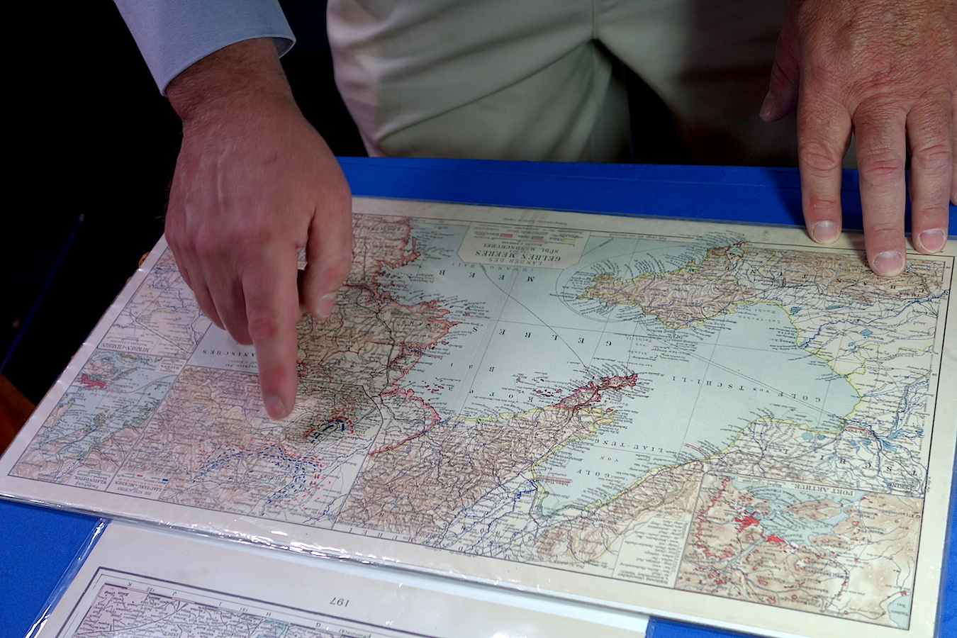 Craig Flinner of Craig Flinner Gallery shows Thompson the battle lines on an antique atlas map of northeast Asia. Click on the image for a larger view.