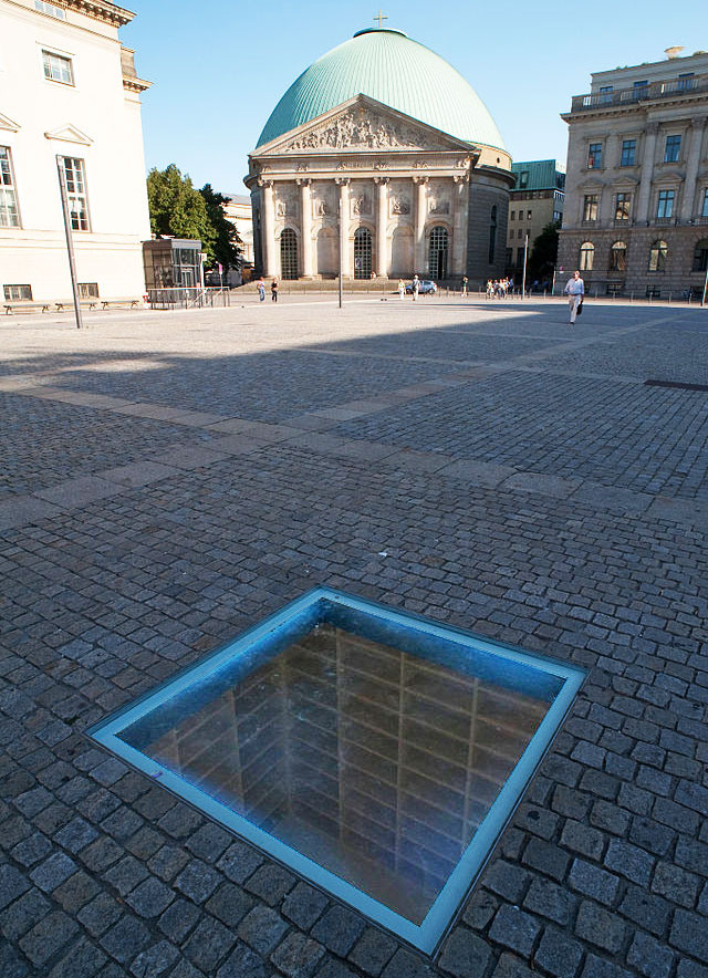 In Berlin's Bebelplatz, this memorial by Micha Ullman recalls the Nazi book-burning of 1933 with its rows of empty shelves permanently sealed in an underground room. (via Wiki Commons)