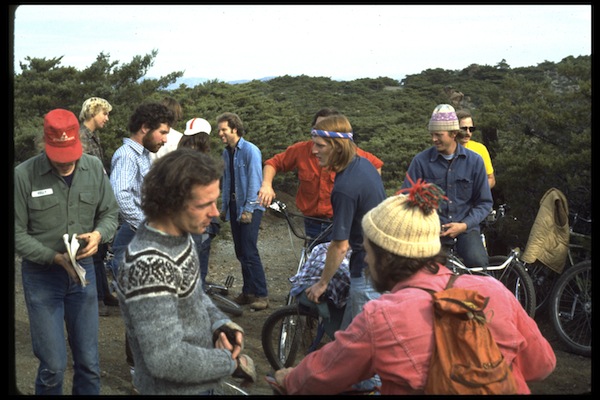 Riders gathered at the top of Repack for this 1977 race include Charlie Kelly (in red hat with notebook), Alan Bonds (wearing a gray sweater in the foreground), Joe Breeze (wearing lots of denim in the background), and Gary Fisher (also in denim, wearing one of his signature ski caps).