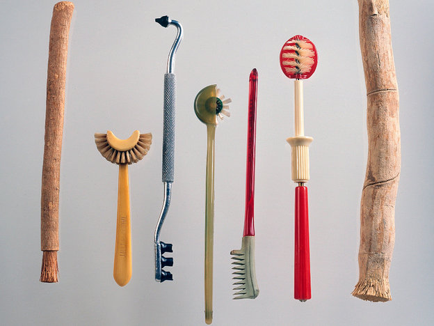 "Top: Various dental extraction methods from J.M. Bourgery's ""Complete Treatise of Human Anatomy,"" circa 1870. Above: Toothbrushes at the National Museum of Dentistry include, from left to right: A miswak or chew stick, an early 20th century celluloid toothbrush by Taub, a rubber-tipped gum stimulator and toothbrush from pre-1945, a Strockway rotary toothbrush from the 1950s, a Dr. Mayland's rubber toothbrush from the 1920s, a 1930s Rotor toothbrush, and another chew stick."
