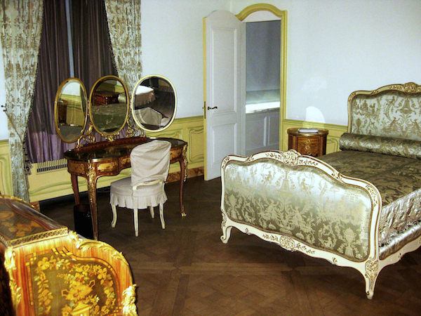 A bedroom inside Huguette Clark's apartment. In the 1990s, Huguette Clark commissioned exact replicas of all her mother's Victorian bedroom furniture including a gray-painted and parcel-gilt bed upholstered in Chinoserie-patterned silk damask, a French ormolu-mounted tulipwood, bois satine, sycamore, and fruitwood marquetry and parquetry dressing table with three folding oval mirrors, and a French ormolu-mounted tulipwood, sycamore, and stained fruitwood marquetry and parquetry bureau a cylindre. (Via the estate of Huguette Clark from EmptyMansionsBook.com)