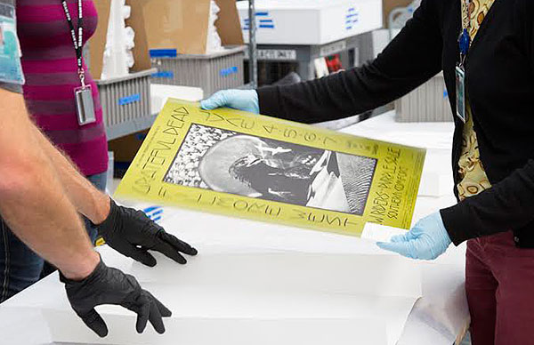 "Preparators at SFO ready a Grateful Dead poster, designed by David Singer and printed by Tea Lautrec Litho, for display in ""When Art Rocked."""
