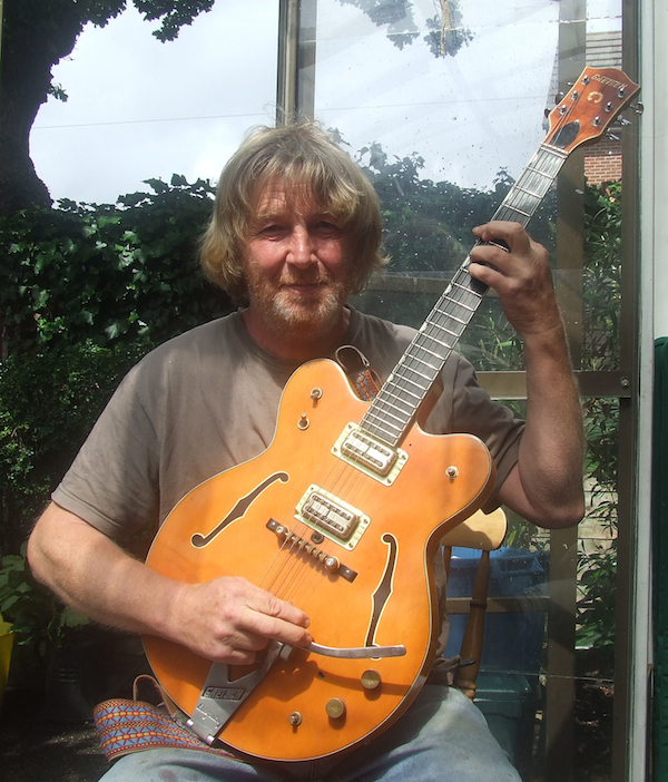 A recent photograph of David Birch, holding the guitar his cousin John Lennon gave him in 1967.
