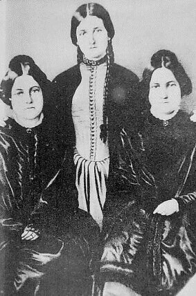 "Above: Margaret, at left, and Kate Fox, with their much-older sister, Leah, right. (WikiCommons) Top: An image of a ghost at a séance in the May 12, 1888, edition of ""Frank Leslie's Illustrated Newspaper."" (Via MysteriousPlanchette.com)"