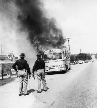 State troopers watch as a Freedom Rider bus burns after being firebombed on May 14, 1961. Via the Birmingham Civil Rights Institute.