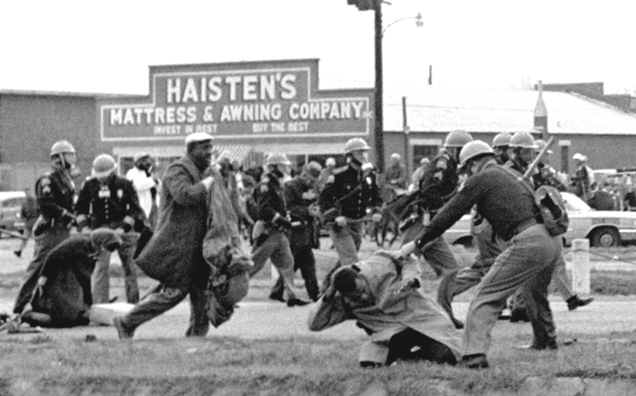 Demonstrators including John Lewis, chairman of SNCC (center), are attacked by policemen during the Selma to Montgomery march in 1965. Via the Library of Congress.