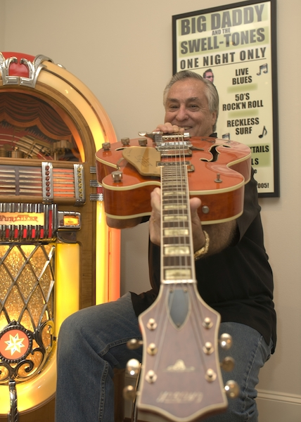 "Bob Wingate, sitting next to his Wurlitzer Bubbler Jukebox, holds a 1956 Gretsch Chet Atkins 6120 guitar. (Via ""Mantiques"")"
