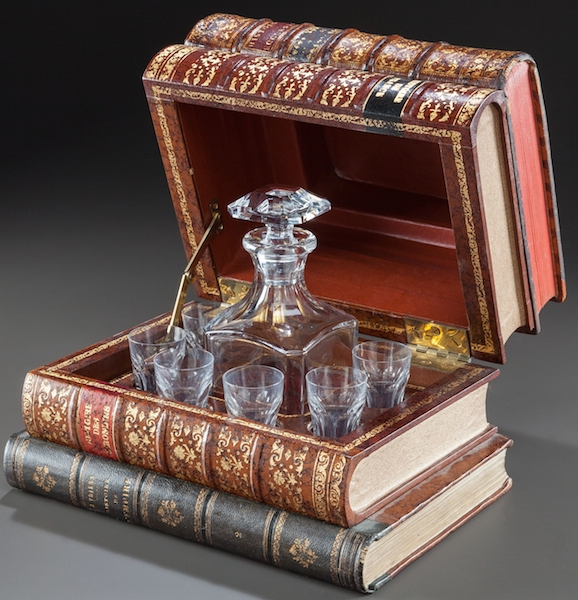 "This faux stack of books holds a 20th century French Baccarat decanter. (Via ""Mantiques"")"