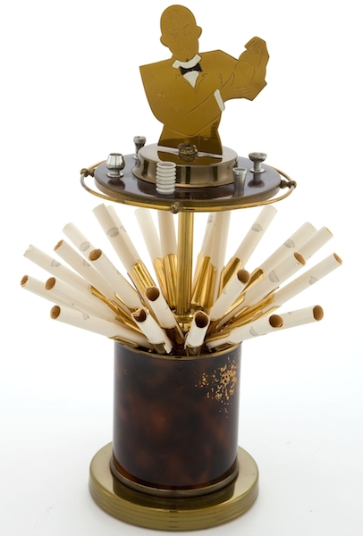 "This Art Deco brass cigarette dispenser, featuring a bartender on top, is filled with cigarette holders. (Via ""Mantiques"")"