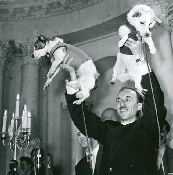 Soviet space researcher Oleg Gazenko holds Strelka (left) and Belka (right) aloft at the 1960 press conference immediately after their landing. In his memoirs, Gazenko referred to this as the proudest moment of his life. (© FUEL Publishing)