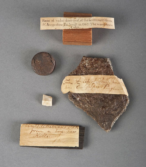 Abby Knight McLane's curio cabinet included a piece of a cedar doorpost from a government building in St. Augustine, Florida; a stone from Mount Pony, Virginia; oak from a bog near Killarney, Ireland; a small white stone from Pompeii, Italy; and a round metal piece from the HMS Great Britain. (Photo by Richard W. Strauss, Smithsonian Institution.)