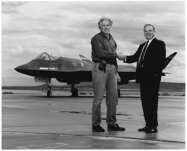 Photographer Bob Seidemann (left) shakes hands with Robert Sandusky, chief designer of the Northrup YF-23 behind them, Edwards Air Force Base, 1991.