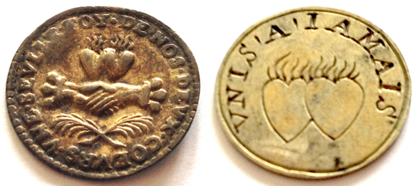 Two examples of treizains, or French marriage medals, from Nancy Rosin's collection.  Both have double flaming hearts, while the coin on the left has a handshake symbolizing a union. (Photos by Nancy Rosin)
