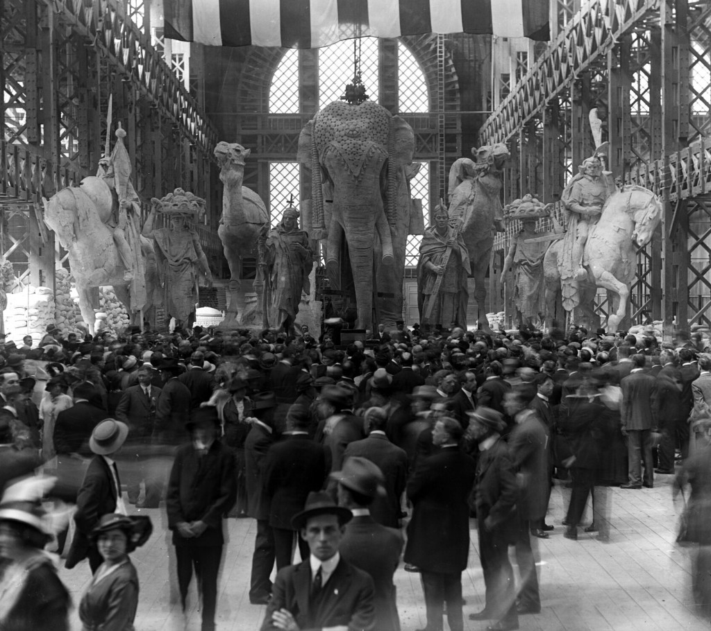 "In one of the unfinished palaced, the sculpture group called ""Nations of the East"" awaits installation over the Arch of the Rising Sun behind a crowd previewing the fairgrounds."