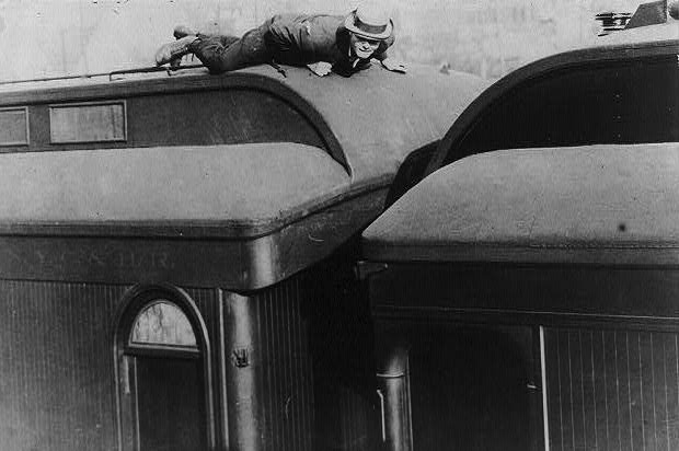 "A man lying prone atop a railroad passenger car in a 1907 photo titled, ""Tramp life—how Jack London traveled on a passenger coach."" (From the Bain Collection, Library of Congress)"