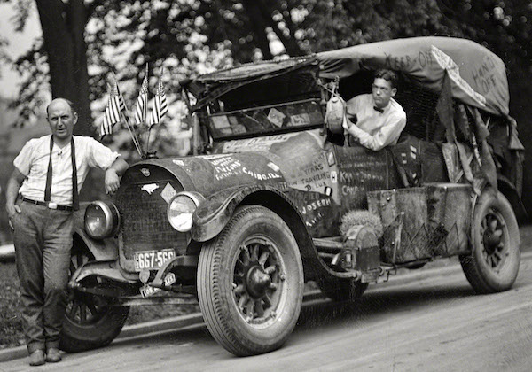 "Jeff Davis, left, and his ""rubber tramp"" car with graffiti, including ""Davis,"" ""Keep Off,"" ""Hobo King,"" ""Hands Off,"" and ""Traveling DeLux,"" in 1924. (From the Harris & Ewing Collection, Library of Congress)"