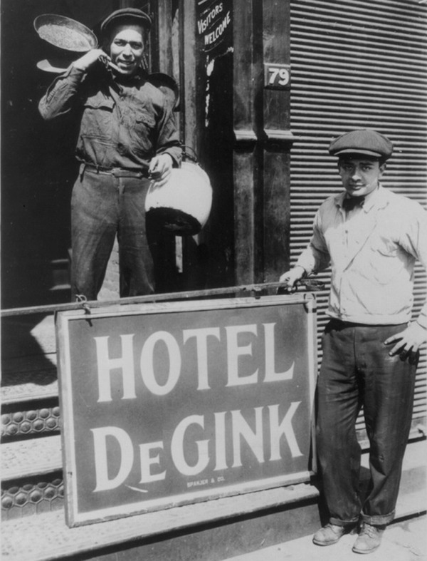 Two men help move a Hotel de Gink, or a hobo shelter run by hoboes, into an old button factory in New York City's Bowery district on April 8, 1915. (From the Bain News Service, Library of Congress)