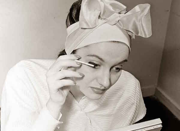 A woman applies makeup at Helena Rubinstein's Fifth Avenue salon. (By Nina Leen/Life Magazine, via Glamour Daze)