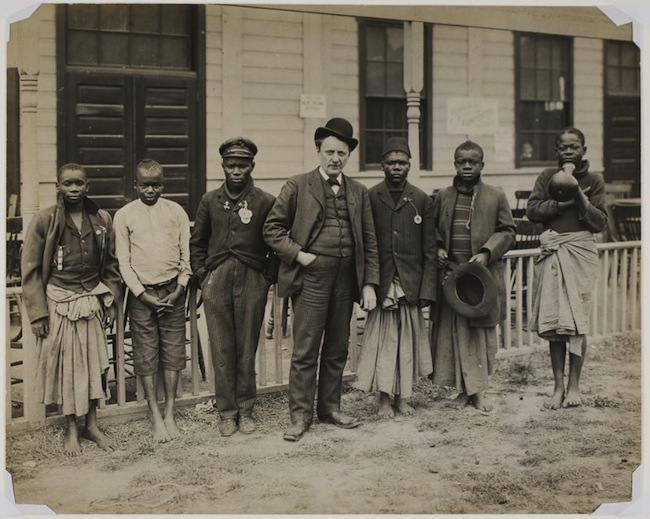 A white tourist poses with a group of black men and boys at the St. Louis World's Fair Philippines exhibit in 1904. Image via the Harvard Art Museums.
