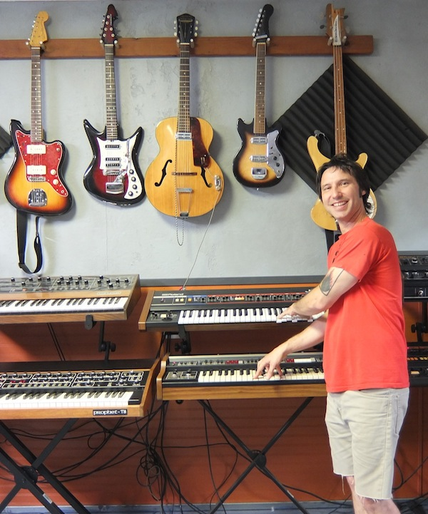 Lance Hill, goofing around with a pair or Roland synthesizers. The vintage guitars on the wall behind him are also used by artists who come to his studio to record.