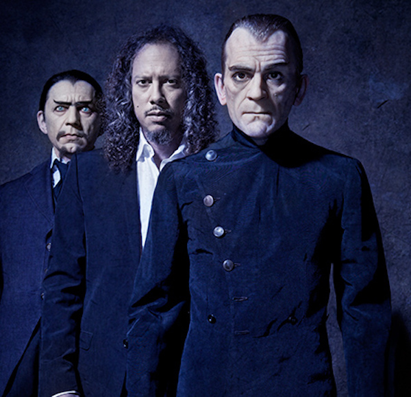 "Hammett stands between a figure of Bela Lugosi, wearing the original vest and jacket from ""White Zombie,"" and a mannequin of Boris Karloff wearing his outfit from ""The Black Cat,"" a movie about a devil-worshipping architect loosely based on Aleister Crowley. (From ""Too Much Horror Business"")"