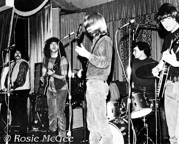 The Grateful Dead performing at Troupers Hall in Los Angeles on March 25, 1966. This show is often listed as an Acid Test, but it was not, according to photographer Rosie McGee. From left to right: Pigpen, Garcia, Lesh, Kreutzmann, and Weir.