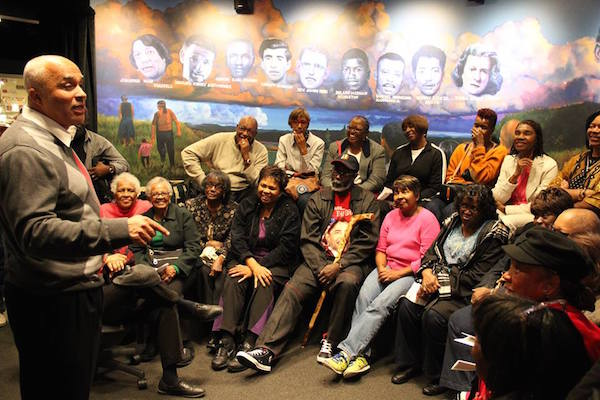 """Dr. David Pilgrim gives a talk to visitors at the Jim Crow Museum. Behind the crowd is part of Jon McDonald's 2012 mural """"Cloud of Witnesses,"""" which honors some of the people who were killed in the 1960s Civil Rights Movement. (From the Jim Crow Museum Facebook page)"""