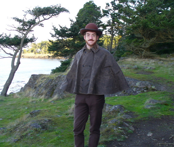 Hiking on Lopez Island, Washington, Gabriel wears a waxed canvas cape, sewn by Katharine Andrews after an 1890s original, and bull-denim pants copied from the 1870s originals.  (From ThisVictorianLife.com)
