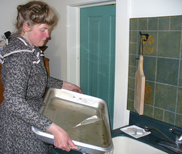 Sarah empties the meltwater from her icebox's drain pan twice a day. (From ThisVictorianLife.com)
