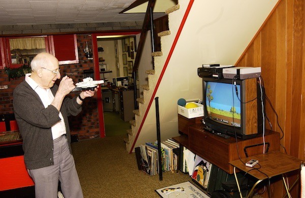 Baer playing a videogame he invented; his basement workshop is in the background.