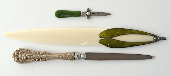 "Top: An assortment of wooden paper-knives from Spellerberg's collection. From top to bottom, bamboo knife with a ruler; a curved (sickle shape) Mauchline ware paper-knife with poker and transfer work; an olive wood paper-knife inscribed ""The Mount of Olives"" in Hebrew; a walnut paper-knife hallmarked 1881 and featuring a wooden soldier's head carved from a palm nut. Above: Letter openers are often made from precious materials. From top to bottom, a greenstone and silver opener from 1903; an Art Nouveau ivory opener with enameled silver; and a letter opener featuring a sterling silver handle."