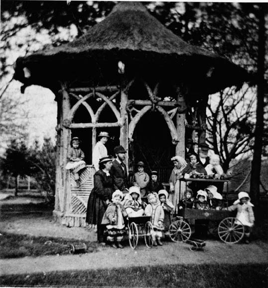 A Oneida közösség gyermekei és gondozóik egy olyan szerkezetet jelentenek, amelyet az 1870-es évek körül körülvett Rustic Summer House-nak hívtak.  (A New York-i Syracuse Egyetemi Könyvtár Oneida közösség gyűjteményéből)
