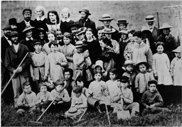 A Oneidans egy csoportja - férfiak, nők és gyermekek - együtt készülnek a gyep tisztításához.  (A New York-i Syracuse Egyetemi Könyvtár Oneida közösség gyűjteményéből)