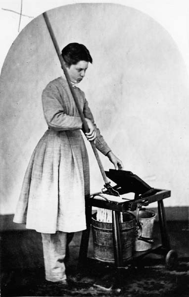 An Oneidan woman named Anna Bolles sports the short hair, plain dress, and pantaloons that were standard in the Community. She's using a mop-wringer invented by Community member John Leonard. (From the Oneida Community Collection at Syracuse University Library in New York)