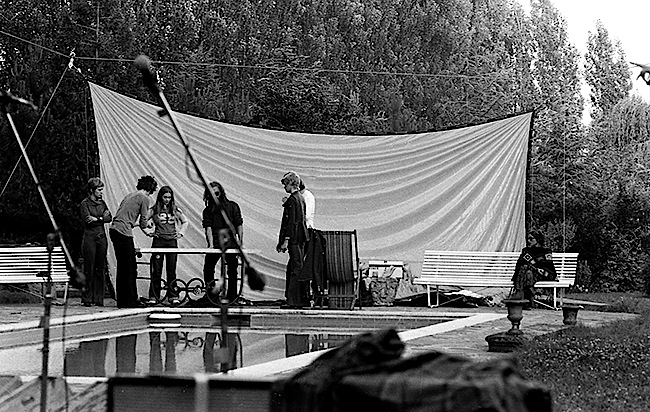 Bill Ham (partially obscured by a microphone stand) and other members of Light Sound Dimension preparing for their poolside performance at Château d'Hérouville in 1971.