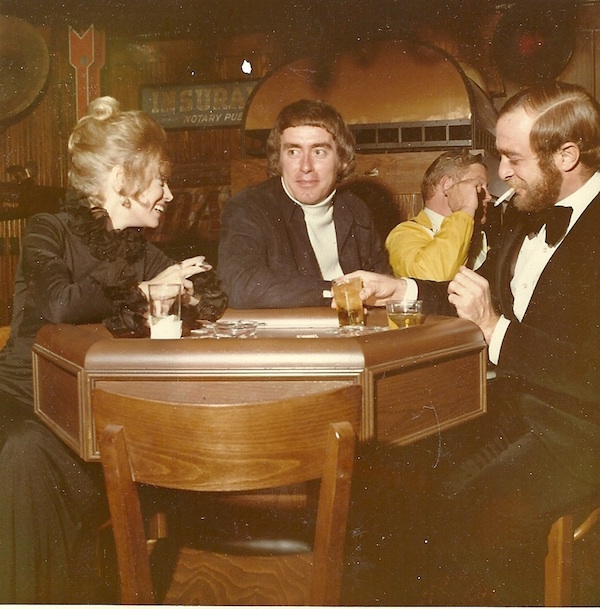 Dan Scoggin (center) in a suede leisure suit, Alan Stillman (right), and an unnamed woman celebrate the opening of T.G.I. Friday's on Greenville Avenue in Dallas in 1972. (Via Friday's Founder)