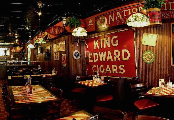 The modern-day T.G.I. Friday's in Prague, Czech Republic, reflects the restaurant's traditional design elements: Tiffany-style lamps, ferns, vintage signs, and candy stripes. (Via Prague-Stay.com)