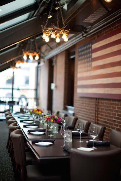 Interesting light fixtures and a folk-art American flag are subtle accents at the elegant Anthem Kitchen and Bar in Boston. (Courtesy of Hospitality Solutions)