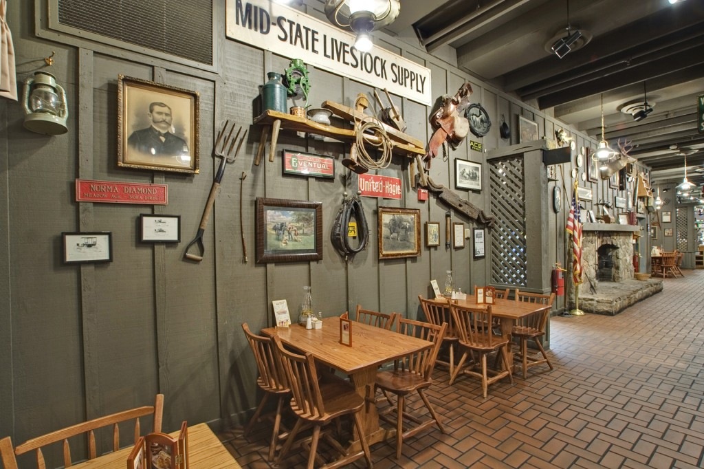 The walls of a Cracker Barrel dining room are adorned with things like old photos, saddles, farm signs, and pitchforks. Click on the image to see a larger version. (Via Cracker Barrel Old Country Store)